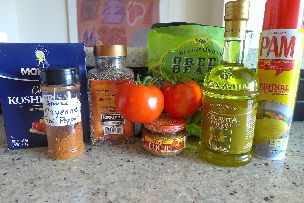 Assemble ingredients: Green beans, fresh tomato, roasted garlic, olive or vegetable oil, vegetable cooking spray, salt, pepper, cayenne (optional)
