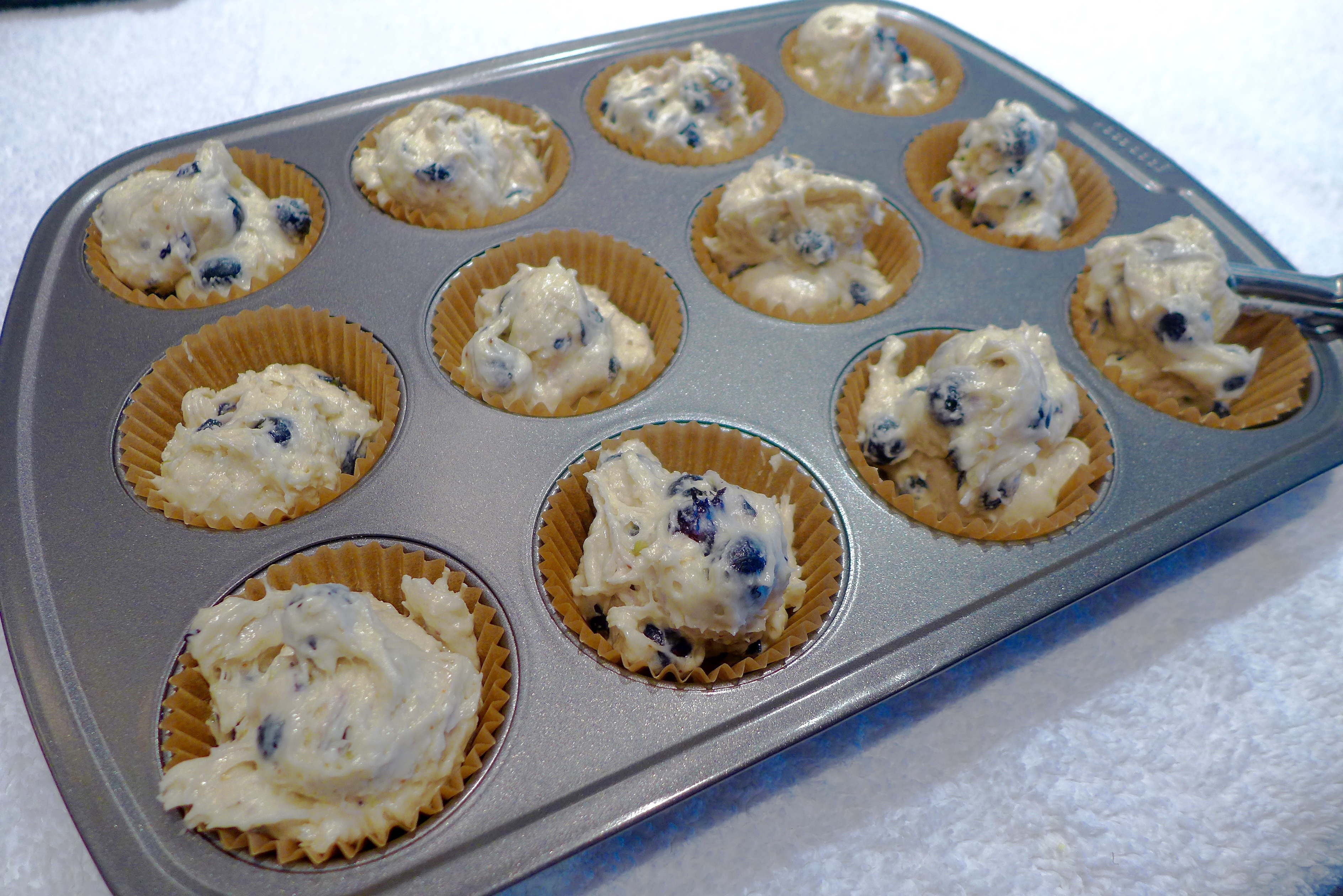 Use a small ice cream scoop or tablespoon to fill muffin cups. Don't worry if batter is slightly above the line of paper. It will settle in as it bakes. The muffins look prettiest if you don't mash down the batter into the cups.